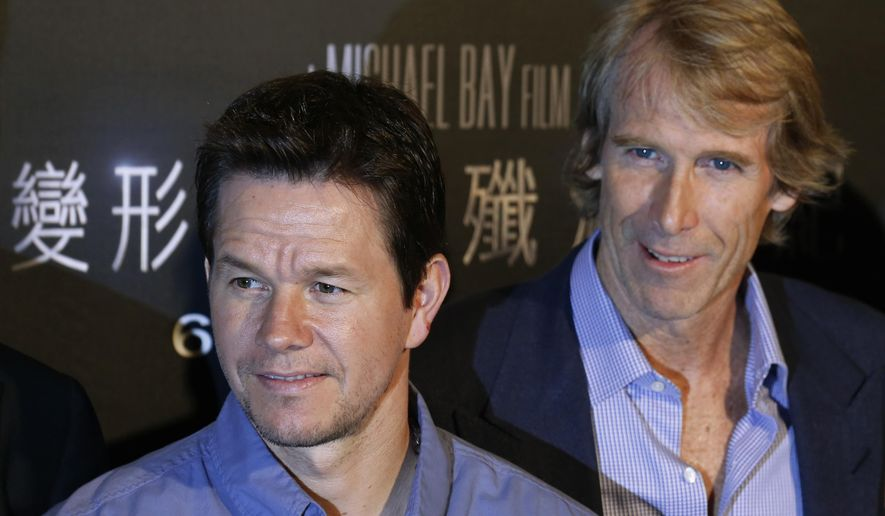 "FILE - American director Michael Bay, right, and actor Mark Wahlberg pose before a news conference on their movie ""Transformers 4: Age of Extinction"" in Hong Kong in this Friday, June 20, 2014 file photo. Wahlberg and Bay reunited Saturday night Jan. 31, 2015 for a charity event that organizers said raised more than $1 million.  (AP Photo/Kin Cheung)"