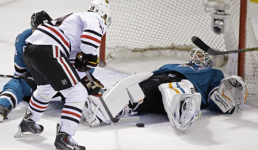 San Jose Sharks goalie Antti Niemi, right, stops a shot by Chicago Blackhawks center Jonathan Toews, left, during the second period of their NHL hockey game Saturday, Jan. 31, 2015, in San Jose, Calif. (AP Photo/Eric Risberg)