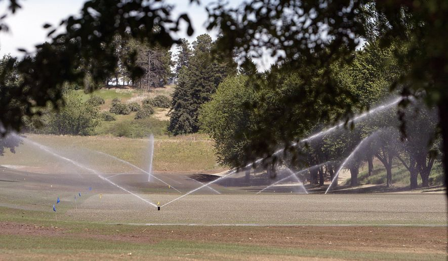 FILE -- In this June 19, 2007 file photo, sprinklers send water over the recently seeded west driving range tee area at the Palouse Ridge golf course at Washington State University in Pullman, Wash. The state Supreme Court in May of 2013 heard arguments in a case involving the use of water from a declining aquifer to irrigate Washington State University's new golf course. Nearly two years later, the court has yet to issue its decision in the case. (AP Photo/Moscow-Pullman Daily News, Dean Hare, File)