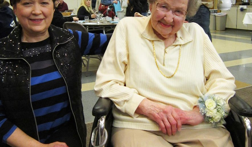 Cathy Mullen sits with Gena Tank on her 100th birthday celebration at First Lutheran Church in Fremont, Neb., on Jan. 18, 2015.  (AP Photo/The Tribune, Betsy Hansen  )