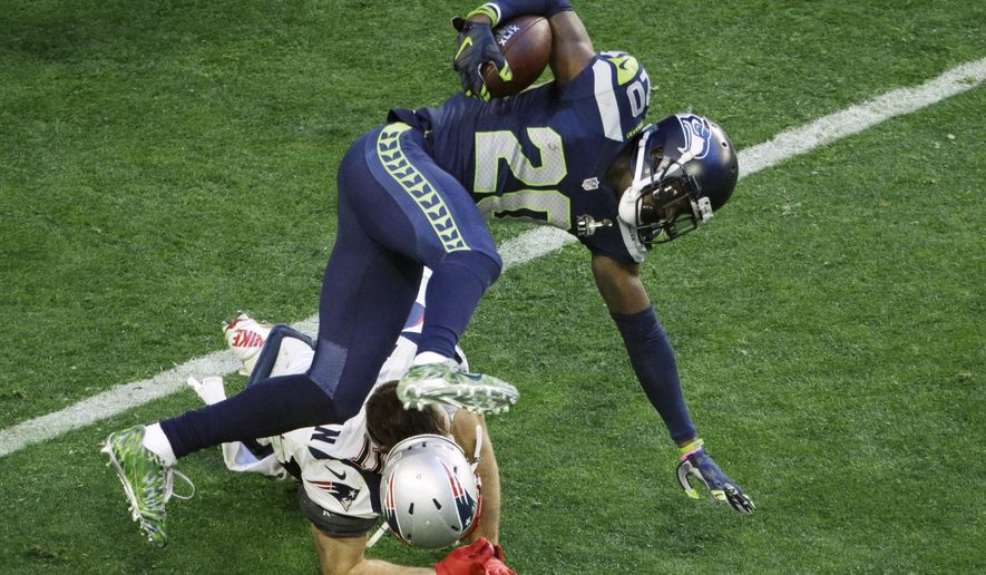 Seattle Seahawks cornerback Jeremy Lane (20) is upended by New England Patriots wide receiver Julian Edelman (11) after an interception during the first half of NFL Super Bowl XLIX football game Sunday, Feb. 1, 2015, in Glendale, Ariz. (AP Photo/Charlie Riedel)