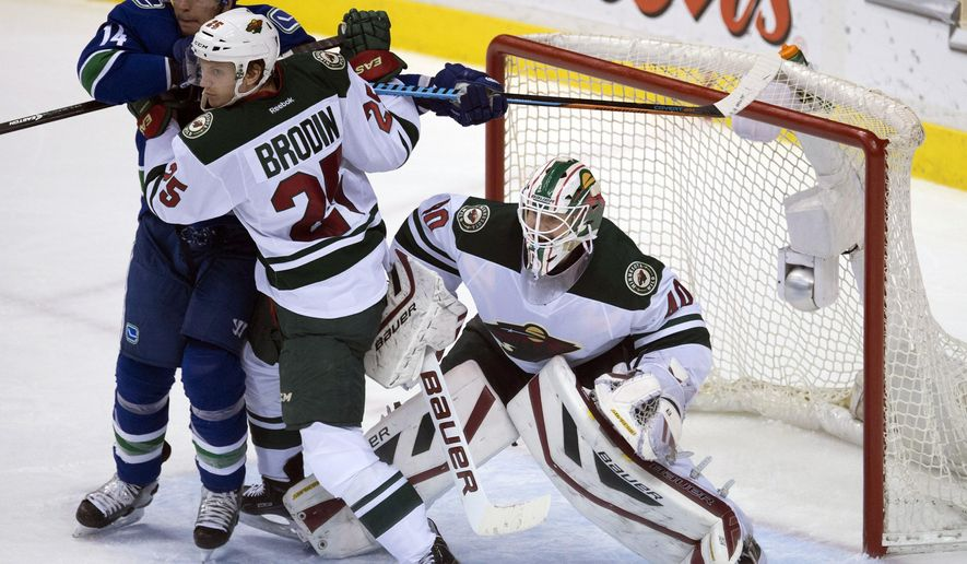 Minnesota Wild defenceman Jonas Brodin (25) tries to clear Vancouver Canucks left wing Alex Burrows (14) from in front of Wild goalie Devan Dubnyk (40) during the second period of NHL action in Vancouver, British Columbia, Canada, Sunday, Feb. 1, 2015. (AP Photo/The Canadian Press, Jonathan Hayward)