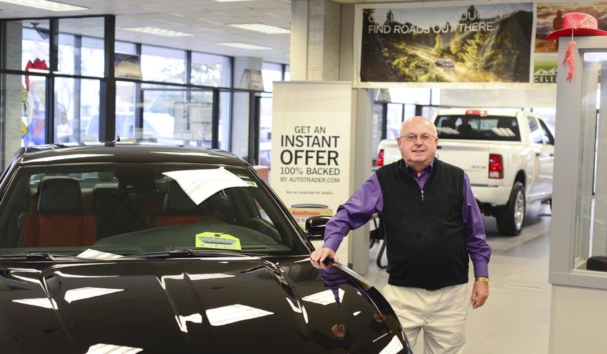 In this photo taken on Jan. 21, 2015, Larry Smalley poses next to an automobile at Cornhusker Auto, in Norwolk, Neb.  Recently, Smalley's co-workers at Cornhusker Auto in Norfolk celebrated his 60th year in the local auto scene by hosting an open house in his honor.  (AP Photo/The Norfolk Daily News, Jake Wragge)