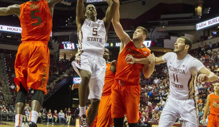 Florida State forward Jarquez Smith gets a shot off between Miami's Davon Reed, left, and Ivan Cruze Uceda in the first half of an NCAA college basketball game in Tallahassee, Fla., Sunday, Feb. 1, 2015. (AP Photo/Mark Wallheiser)