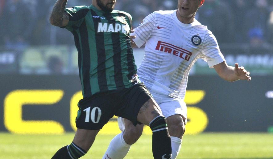 Sassuolo's Simone Zaza, left, vies for the ball with Inter Milan's Nemanja Vidic, during their Serie A soccer match at Reggio Emilia's Mapei stadium, Italy, Sunday, Feb. 1, 2015. (AP Photo/Marco Vasini)