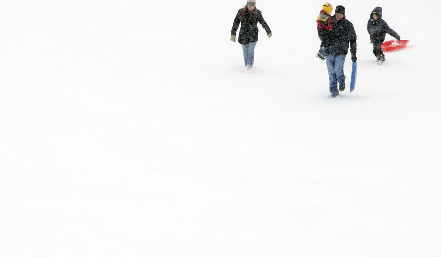 People make their way up the hill at Twin Sister Hills Park, Sunday, Feb. 1, 2015, in Rockford, Ill. A slow-moving winter storm blanketed a large swath of the Plains and Midwest in snow Sunday, forcing the cancellation of more than 1,500 flights and making roads treacherous. (AP Photo/Rockford Register Star, Max Gersh)  MANDATORY CREDIT