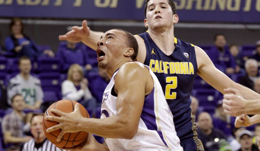 Washington's Andrew Andrews drives to the basket past California's Sam Singer in the first half of an NCAA college basketball game on Sunday, Feb. 1, 2015, in Seattle. (AP Photo/John Froschauer)