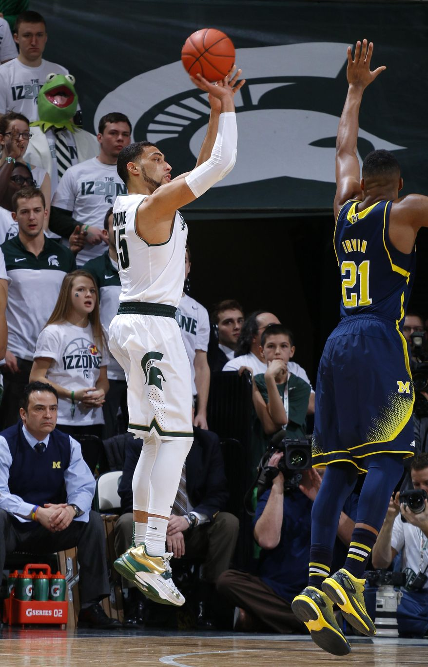 Michigan State's Denzel Valentine, left, shoots a 3-pointer against Michigan's Zak Irvin (21) during the first half of an NCAA college basketball game, Sunday, Feb. 1, 2015, in East Lansing, Mich. (AP Photo/Al Goldis)