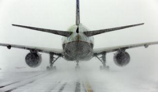 A United Airlines jet blows snow on a runway at O'Hare International Airport, Sunday, Feb. 1, 2015, in Chicago. More than 1,100 flights have been canceled at Chicago's airports and snow-covered roads are making travel treacherous. (AP Photo/Nam Y. Huh)