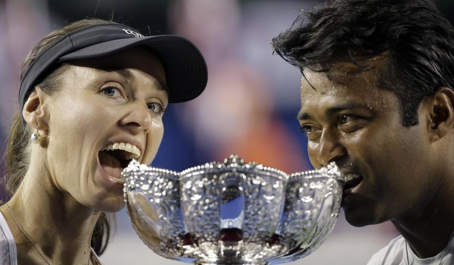 Martina Hingis of Switzerland, left,  and Leander Paes of India pose with the trophy after defeating Kristina Mladenovic of France and Daniel Nestor of Canada in the mixed doubles final at the Australian Open tennis championship in Melbourne, Australia, Sunday, Feb. 1, 2015. (AP Photo/Bernat Armangue)