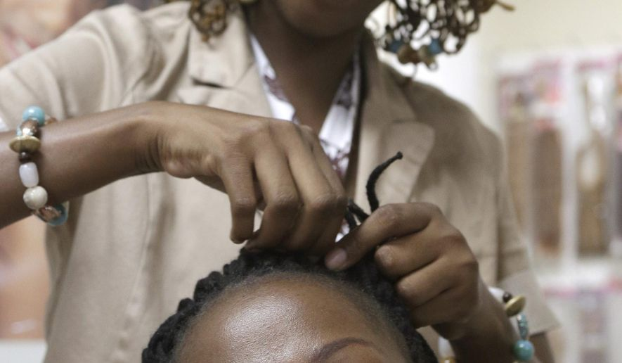 FILE - In this June 17, 2014, file photo, Nivea Earl, top, braids Christine McLean's hair in McLean's Little Rock, Ark., shop. An upcoming vote by legislators in Arkansas could end a federal lawsuit claiming the state unfairly discriminates against African-style hair braiders. (AP Photo/Danny Johnston, File)