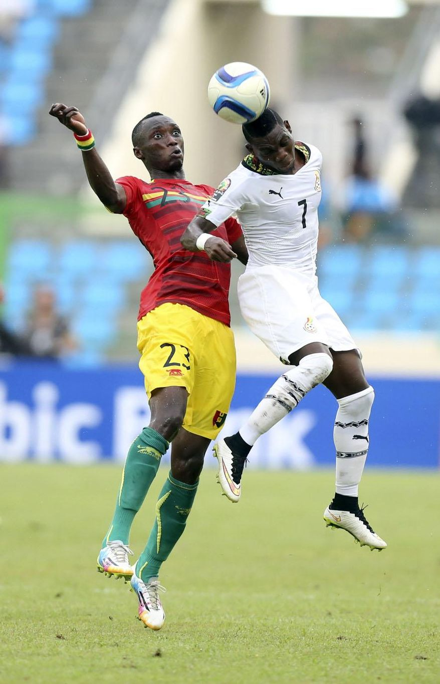 Ghana's Christian Atsu, right, is tackled by Guinea's Djibril Tamsir Paye during their African Cup of Nations quarter final soccer match at the Estadio De Malabo, Equatorial Guinea, Sunday, Feb. 1, 2015. (AP Photo/Sunday Alamba)