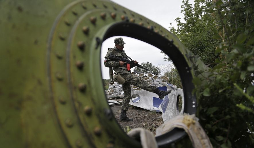 A Pro-Russian rebel looks at pieces of the Malaysia Airlines Flight 17 plane near village of Rozsypne, eastern Ukraine, in this Sept. 9, 2014, file photo. (AP Photo/Sergei Grits, File)