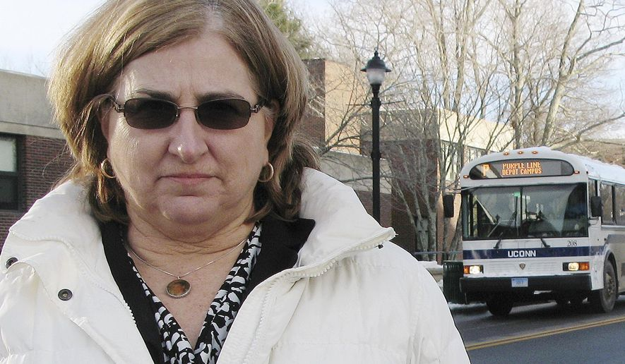 In this Jan. 29, 2015 photo, Linda Plamondon of Westminster, Mass., poses near a UConn transit bus on Hillside Road on the school's campus in Storrs, Conn. Plamondon, whose son David was struck and killed by a bus on campus in 2011, is pushing for reforms to the school's bus system. She said the school has not done enough since then to improve pedestrian safety and wants it to stop using students as bus drivers. (AP Photo/Pat Eaton-Robb)