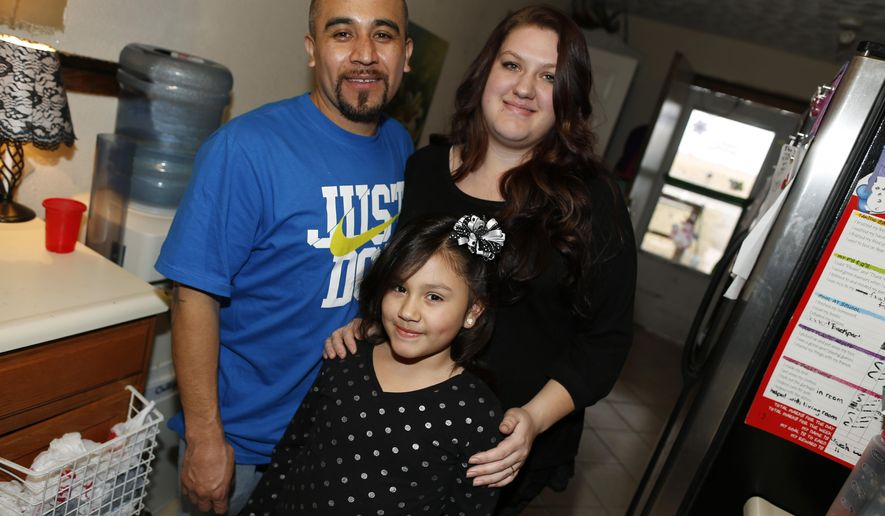 Maximiano Vazquez-Guevara, left, his wife Ashley Bowen, and their 6-year-old daughter, Nevaeh Vazquez, pose for a photo in their home Saturday, Jan. 31, 2015, in the northeast Denver suburb of Commerce City, Colo. The presidential executive order that fast-tracked immigration hearings for last summer's flood of Central American migrants may have had unintended consequences in canceling hearings for non-detained immigrants with longstanding cases such as Vazquez-Guevara. Vazquez-Guevarra, 34, recently won his appeal to become a legal permanent resident. But his case still needs to go in front of an immigration judge one last time, and it has been pulled from the docket.  Thousands of immigrants seeking legalization through the U.S. court system have had their hearings canceled and are being told by the government that it may be 2019 or later before their futures are resolved.  (AP Photo/David Zalubowski)