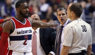 Washington Wizards guard John Wall (2) tries to calm coach Randy Wittman as he comes to talk with referee John Goble during the second half of an NBA basketball game against the Toronto Raptors, Saturday, Jan. 31, 2015, in Washington. The Raptors won 120-116 in overtime. (AP Photo/Alex Brandon)