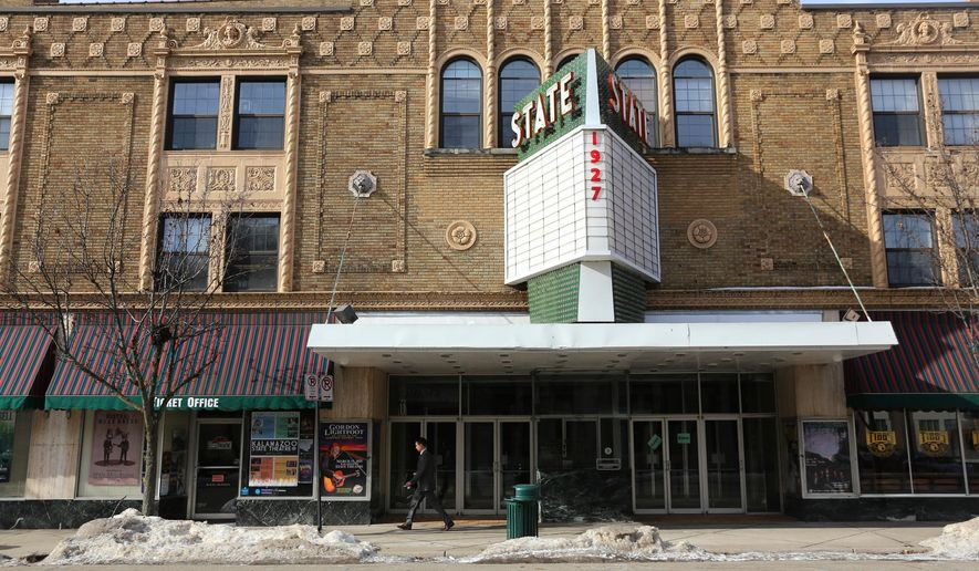 In this Jan. 26, 2015 photo, a passerby walks in front of the marquee of the historic State Theatre, in Kalamazoo, Mich. The theater is undergoing renovations, including refurbishment of the marquee, removing old curtains, rearrangement of seating, repairing dressing rooms and removing old fixtures. (AP Photo/Kalamazoo Gazette-MLive Media Group, Mark Bugnaski) ALL LOCAL TELEVISION OUT; LOCAL TELEVISION INTERNET OUT