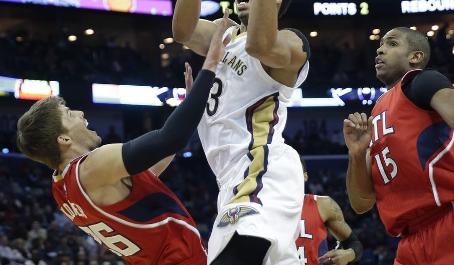New Orleans Pelicans forward Anthony Davis fouls Atlanta Hawks guard Kyle Korver, left, as he drives to the basket in front of center Al Horford (15) in the first half of an NBA basketball game in New Orleans, Monday, Feb. 2, 2015. (AP Photo/Gerald Herbert)