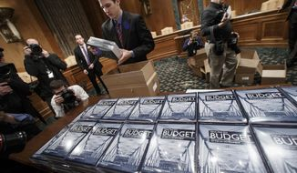 President Barack Obama's new $4 trillion budget plan is distributed by Senate Budget Committee staffer Eric Chalmers as it arrives on Capitol Hill in Washington, early Monday, Feb. 02, 2015. The fiscal blueprint for the budget year that begins Oct. 1, seeks to raise taxes on wealthier Americans and corporations and use the extra income to lift the fortunes of families who have felt squeezed during tough economic times. Republicans, who now hold the power in Congress, are accusing the president of seeking to revert to tax-and-spend policies that will harm the economy while failing to do anything about soaring spending on government benefit programs. (AP Photo/J. Scott Applewhite)