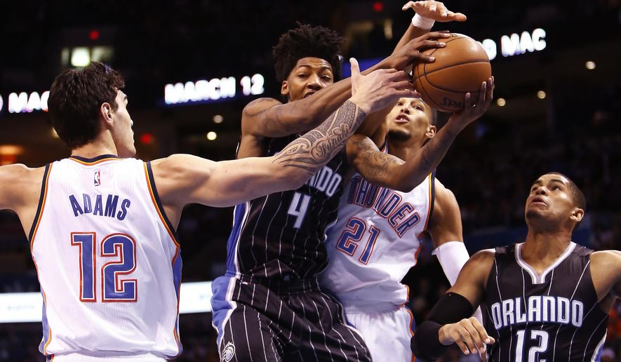 Orlando Magic guard Elfrid Payton (4) gets caught between Oklahoma City Thunder center Steven Adams (12) and Oklahoma City Thunder guard Andre Roberson (21) on the way to the basket during the first quarter of a NBA basketball game in Oklahoma City, Monday, Feb. 2, 2015.  (AP Photo/Alonzo Adams)