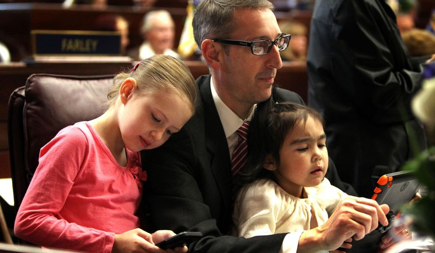 Nevada Sen. Scott Hammond plays video games with his two daughters Sofia and Isabella prior to the opening session of the Nevada Legislature in Carson City, Nev., Monday, Feb. 2, 2015. (AP Photo/Lance Iversen)
