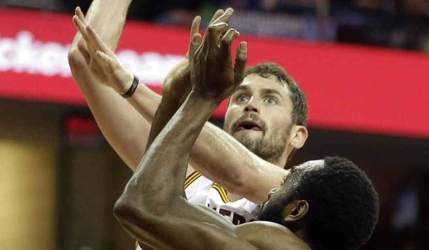 Cleveland Cavaliers' Kevin Love (0) shoots over Philadelphia 76ers' Luc Richard Mbah a Moute, from Cameroon, in the first quarter of an NBA basketball game Monday, Feb. 2, 2015, in Cleveland. (AP Photo/Mark Duncan)