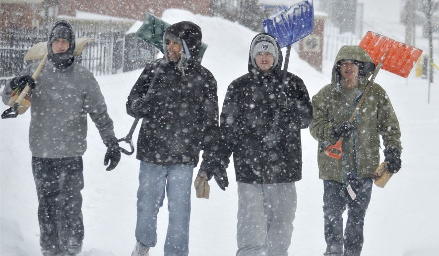Jake Hebert, Derek Colter, Chirs Keefner and John Jones walk on First Street in Pittsfield, Mass., after a morning of shoveling snow during a snowstorm, Monday Feb. 2, 2015. Wind-blown snow started falling in the early hours of Monday and was expected to continue for most of the day. (AP Photo/The Berkshire Eagle, Ben Garver)