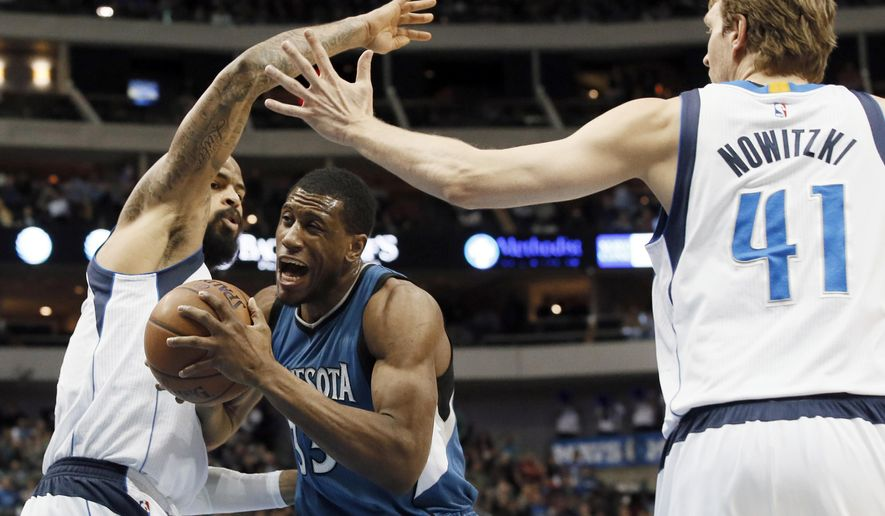 Dallas Mavericks' Tyson Chandler, left, and Dirk Nowitzki (41), of Germany, are unable to stop Minnesota Timberwolves' Thaddeus Young (33) as Young drives to sink a basket in the first half of an NBA basketball game, Monday, Feb. 2, 2015, in Dallas. (AP Photo/Tony Gutierrez)