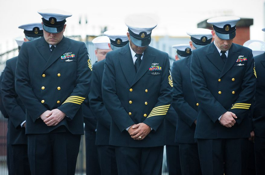 Members of the Navy bow heads during the reopening ceremony at the Washington Navy Yard. Twelve were killed and four wounded during the shooting. (Associated Press)