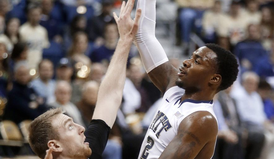 Pittsburgh's Michael Young (2) shoots over Bryant's Andrew Scocca (14) in the first half of an NCAA college basketball game Monday, Feb. 2, 2015, in Pittsburgh. (AP Photo/Keith Srakocic)