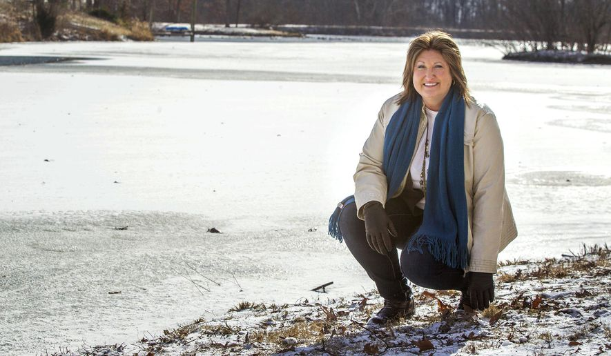 """In this Jan. 7, 2015 photo, Karen Kohler Kaiser kneels by a frozen pond on her property in Waterloo, Ill,. Kaiser wrote the book """"Frozen Grief"""" about how she coped with the sudden death of her sister Kathy Baxmeyer, 40, and her nephew Kadin, 7, who both drowned Feb. 19, almost five years ago, in a frozen pond on the property of her sister Kathy's home in Waterloo.  (AP Photo/Belleville News-Democrat, Derik Holtmann)"""