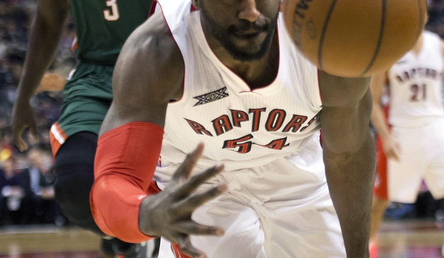 Toronto Raptors forward Patrick Patterson, front, dives to try and keep the ball in play past Milwaukee Bucks forward Johnny O'Bryant (3) during first half of an NBA basketball game in Toronto, Monday, Feb. 2, 2015. (AP Photo/The Canadian Press, Nathan Denette)
