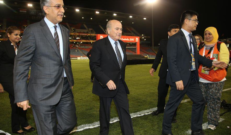 FIFA President Sepp Blatter, center, walks with AFC President  Shaikh Salman bin Ebrahim Al Khalifa, left, after the medal ceremony following the AFC Asian Cup 3rd place playoff soccer match between Iraq and United Arab Emirates in Newcastle, Australia, Friday, Jan. 30, 2015. (AP Photo/Rick Rycroft)