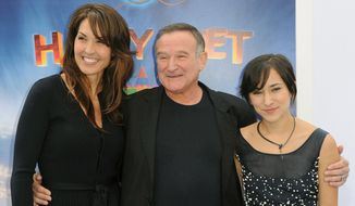 "In this Nov. 13, 2011, file photo, Susan Schneider, from left, Robin Williams, and Zelda Williams arrive at the premiere of ""Happy Feet Two"" at Grauman's Chinese Theater, in Los Angeles. Williams' children and wife are fighting over the late comedian's estate in a California court. In papers filed in December 2014 in San Francisco Superior Court, Williams' wife, Susan, accuses the comedian's children from two previous marriages of taking items without her permission. (AP Photo/Katy Winn, File)"