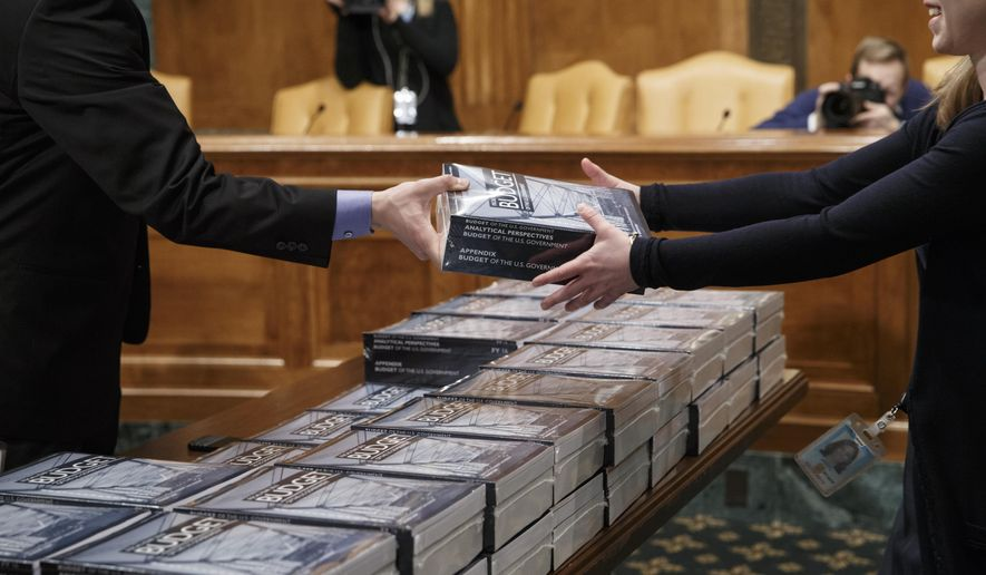 President Barack Obama's new $4 trillion budget plan is distributed by the Senate Budget Committee as it arrives on Capitol Hill in Washington, early Monday, Feb. 02, 2015. The fiscal blueprint for the budget year that begins Oct. 1, seeks to raise taxes on wealthier Americans and corporations and use the extra income to lift the fortunes of families who have felt squeezed during tough economic times. Republicans, who now hold the power in Congress, are accusing the president of seeking to revert to tax-and-spend policies that will harm the economy while failing to do anything about soaring spending on government benefit programs. (AP Photo/J. Scott Applewhite)