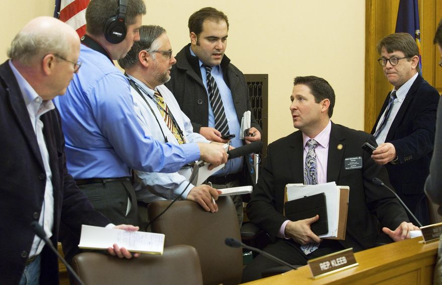 House Appropriations Chairman Rep. Ron Ryckman, Jr., R-Olathe, seated, speaks with reporters after the committee voted to replace the contents of a bill which passed the Senate, Monday, Feb. 2, 2015, at the Capitol in Topeka, Kan. (AP Photo/Topeka Capital-Journal, Thad Allton)