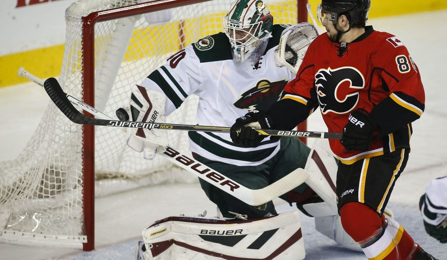 Minnesota Wild goalie Devan Dubnyk, left, swtas the puck away from Calgary Flames Josh Jooris during first period NHL hockey action in Calgary, Thursday, Jan. 29, 2015. (AP Photo/The Canadian Press, Jeff McIntosh)