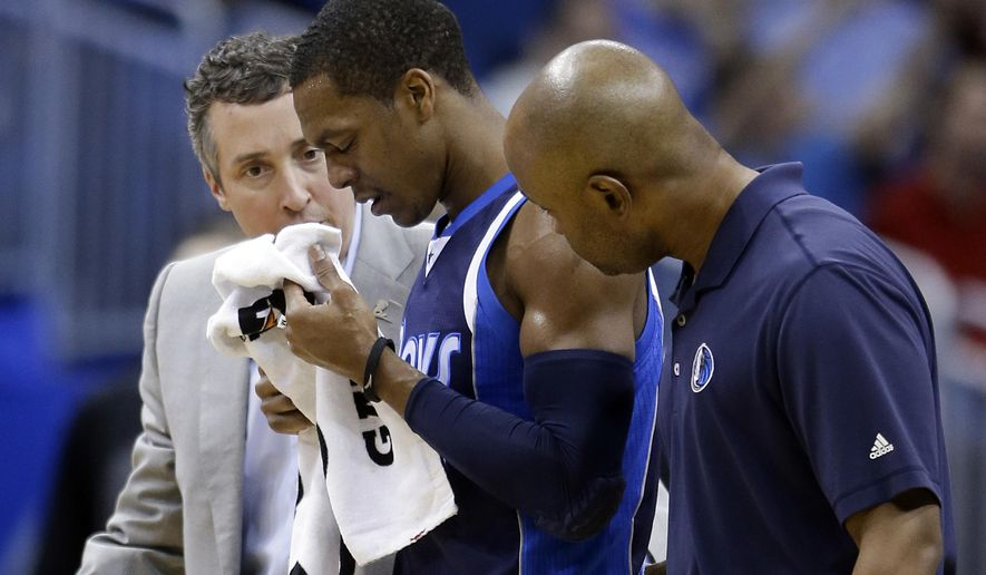 Dallas Mavericks' Rajon Rondo, center, is escorted to the locker room after he was injured during the opening moments of the first quarter of an NBA basketball game against the Orlando Magic, Saturday, Jan. 31, 2015, in Orlando, Fla. (AP Photo/John Raoux)