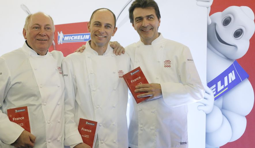 French chefs Rene, left, and his son Maxime Meilleur, center, who run La Bouitte restaurant in the French Alps, and Yannick Alleno, who runs Le Pavilon Ledoyen restaurant in Paris, pose after being awarded three stars with the Michelin guide, Monday, Feb.2, 2015 in Paris. Two restaurants were newly awarded with the prestigious 3 stars this year. (AP Photo/Francois Mori)