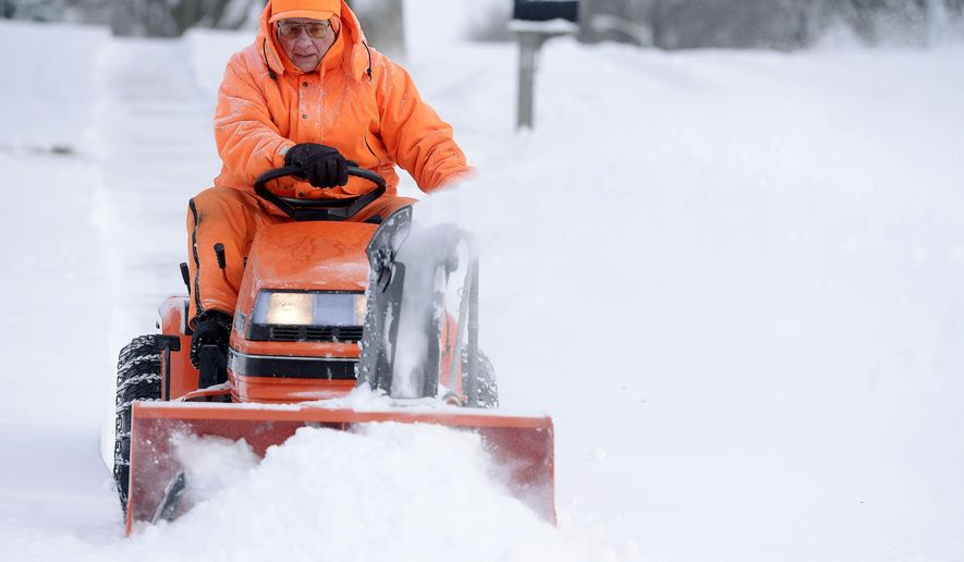 Floyd Larsen clears snow from a neighbor's sidewalk along 33rd Street near Melanie Ave in southeast Sioux Falls Sunday, Feb. 1, 2015,  after a winter storm dropped more than 6 inches of snow in the city. (AP Photo/Argus Leader, Elisha Page)