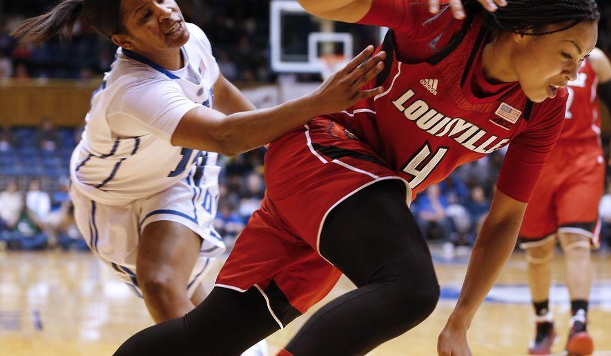 Duke's Ka'lia Johnson, left, knocks the ball away from Louisville's Mariya Moore during the second half of an NCAA college basketball game Monday, Feb. 2, 2015, in Durham, N.C. (AP Photo/Ellen Ozier)
