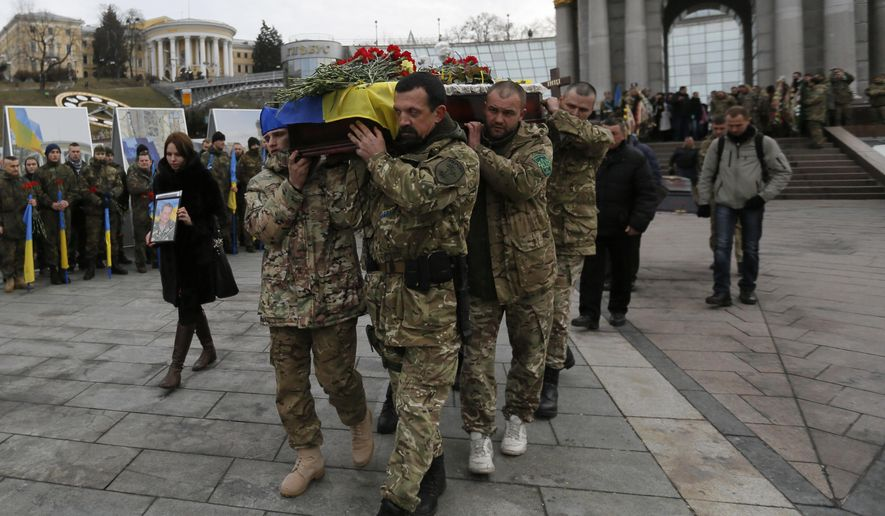 Ukrainian soldiers carry the coffin bearing the body of serviceman Ruslan Baburov, who was killed in fighting against Russian-backed separatists, during a commemoration ceremony in Independence Square in Kiev, Ukraine, on Monday, Feb. 2, 2015. Ukraine's government said Sunday that 13 of its troops were killed and another 20 wounded in a day of fighting across the east. (AP Photo/Sergei Chuzavkov)