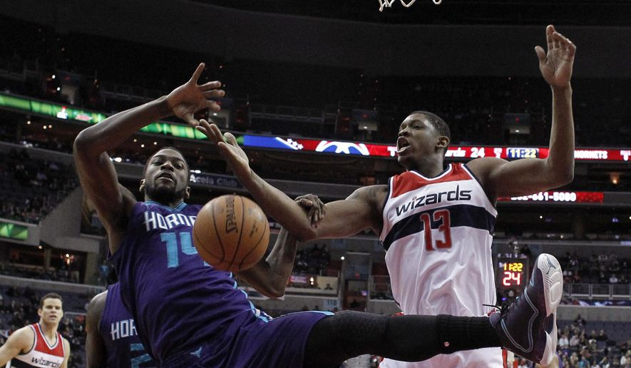 Charlotte Hornets forward Michael Kidd-Gilchrist (14) and Washington Wizards center Kevin Seraphin (13), from France, go for the rebound in the first half of an NBA basketball game, Monday, Feb. 2, 2015, in Washington. (AP Photo/Alex Brandon)