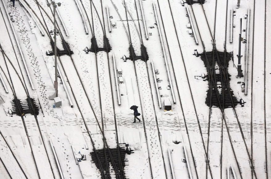 A person crosses snow-covered tracks in a commuter train yard, in New York, Monday, Feb. 2, 2015. The city may get 2 to 4 inches of snow, and ice is possible. (AP Photo/Richard Drew)