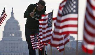 With the Capitol in the background, Army veteran David Dickerson of Oklahoma City, Okla., joins others to place 1,892 flags representing veteran and service members who have died by suicide to date in 2014, on the National Mall in Washington on March 27, 2014. (Associated Press) **FILE**