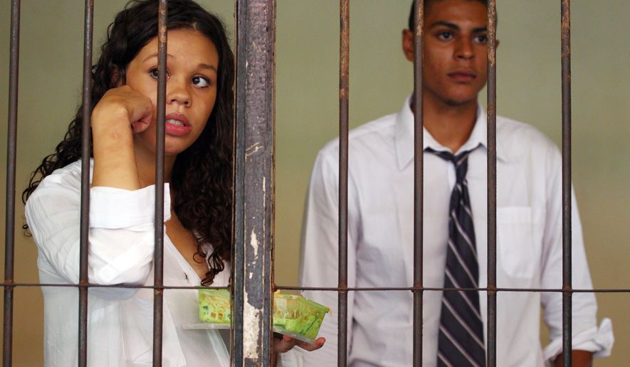 Heather Mack, right, and her boyfriend Tommy Schaefer, 21, both of Chicago, Ill., stand behind bars during their trials in Bali, Indonesia, Monday, Feb. 2, 2015. The couple is charged with murdering Mack's mother, Sheila von Wiese-Mack, 62. (AP Photo/Firdia Lisnawati)