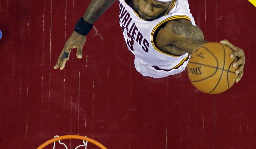 Cleveland Cavaliers' LeBron James dunks against the Philadelphia 76ers in the first half of an NBA basketball game Monday, Feb. 2, 2015, in Cleveland. (AP Photo/Mark Duncan)