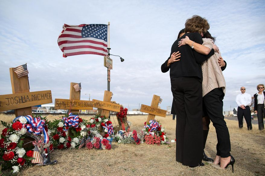 FILE - In this Jan. 29, 2015 file photo, Tiffany Lubbers, back, Angela Boivin, left, and Catherine Stouffer, rigth, widows of veterans killed in the 2012 crash of a freight train and a veterans' parade float, embrace at a makeshift memorial in Midland, Texas. A ruling is expected Monday, Feb. 2, 2015 from a Midland judge on whether to dismiss a lawsuit arising from the crash that killed four veterans and injured about a dozen. Twenty-six people reached a confidential settlement this month with Union Pacific. (AP Photo/The Odessa American, Courtney Sacco, File)
