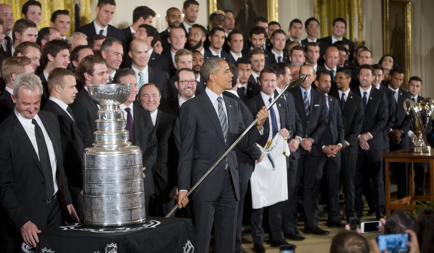 President Barack Obama, center, looks over an engraved hockey stick that was presented to him during a ceremony honoring both 2014 NHL Champion Los Angeles Kings and 2014 MLS Cup Champion LA Galaxy in the East Room of the White House in Washington, Monday, Feb. 2, 2015. (AP Photo/Pablo Martinez Monsivais )