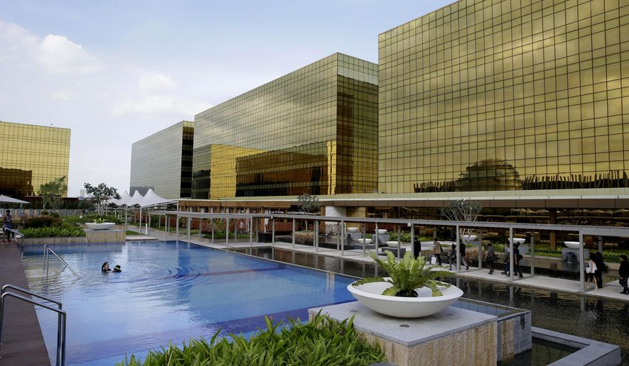 Guests enjoy swimming in a pool at the newly-opened City of Dreams Manila casino Monday, Feb. 2, 2015 at the reclaimed prime property in Manila, Philippines. The company's co-chairmen, Lawrence Ho and Australian billionaire James Packer, led its grand opening Monday, the latest gaming and entertainment resort to have opened in the country. (AP Photo/Bullit Marquez)
